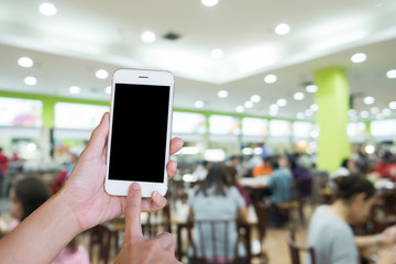 Hands woman are holding touch screen smart phone,tablet on blurred food restaurant.