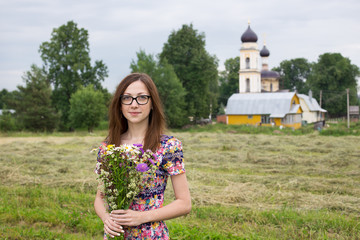Girl with bouquet on background of village church