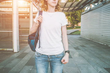 Cropped image. Front view. Young woman with a backpack, wearing a white T-shirt and blue jeans, standing outdoors. Summer sunny evening.