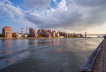 Roosevelt Island with new blocks of housing lying on the edge of East River and the Ed Koch Queensboro Bridge in the background lid by the late afternoon sun
