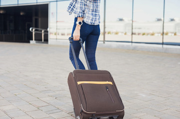 Closeup of young woman walking with luggage suitcase. Vacations, travel and active lifestyle concept