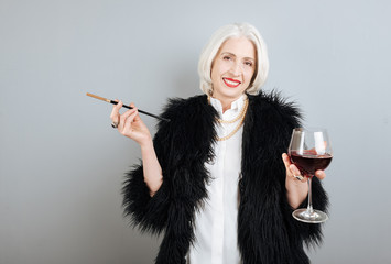 Smiling senior woman drinking wine and smoking.