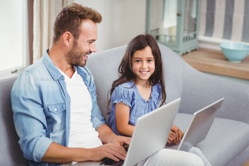 Happy father and daughter using laptop on sofa