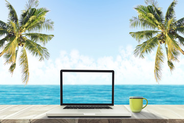 A laptop and a coffee cup on wood table in the sea beach with coconut tree.