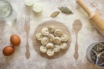 Uncooked dumplings, ravioli on the print plate in the flour, imp