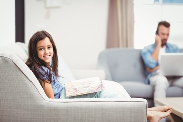 Girl with picture book while father in background