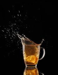Splash of tea with lemon on a black background.