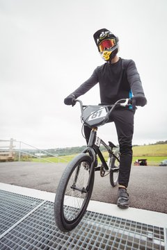 Cyclist preparing for BMX racing at starting ramp