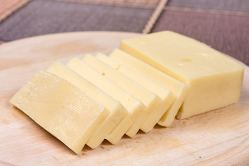Sliced yellow pizza cheese on the wooden cutting board
