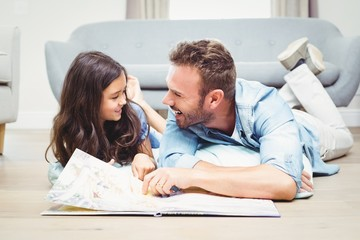 Daughter and father with picture book lying on floor