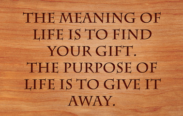 The meaning of life is to find your gift. The purpose of life is to give it away - quote by unknown author on wooden red .oak background