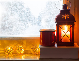 Winter windowsill decor with lantern, book and hot chocolate or