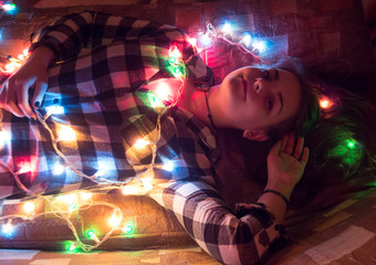 a young girl is highlighted by the light from the garland. creativity