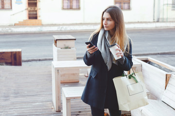 Fashionable woman with purchases uses her mobile phone on the street