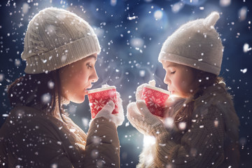 Mother and girl drinking tea