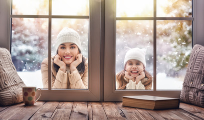 Child and mom looking in windows, standing outdoors