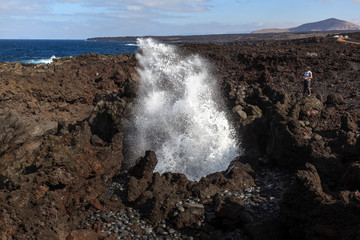 Boiling sea water. Volcanic coastline.