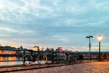 Evening view of parked bicycles alongside the Dutch river Maas