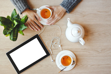 Girl sitting at the table and drinks green tea. Tablet with blank space and headphones lies nearby. Top view