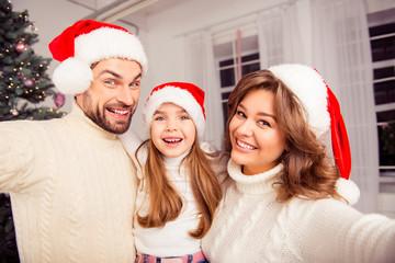 Christmas selfie of smiling family wearing santa hats
