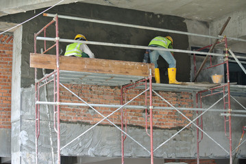 SEPANG, MALAYSIA -OCTOBER 15, 2016: Construction workers plastering wall and beam using cement plaster at the construction site in Sepang, Malaysia