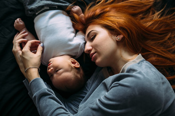 Happy mother with baby lying together on bed