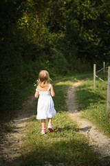Rear View Of Girl Walking On Grassy Pathway