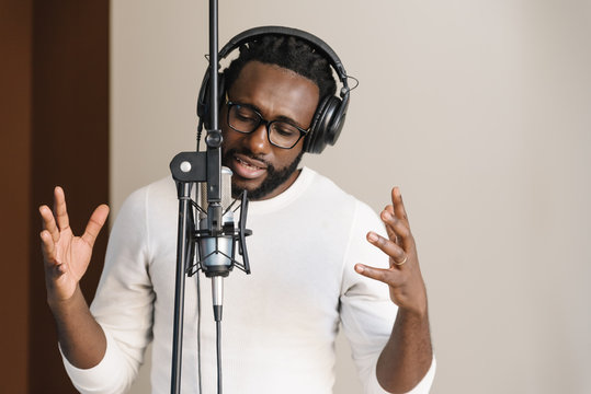 African young man singing on musical studio.