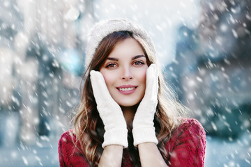 Young beautiful happy smiling girl walking on the street. Model looking at camera, touching her face, wearing stylish knitted hat and gloves. Christmas, New Year, winter holidays concept. Close up