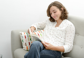 beautiful young woman with a book in the sofa