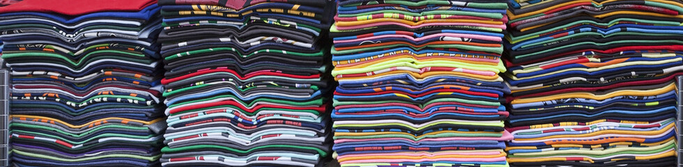 Stacked rows of colorful souvenir t-shirts. Horizontal.