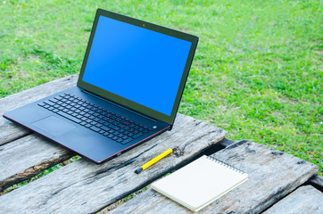 Laptop, notebook and pen on wooden table in greensward