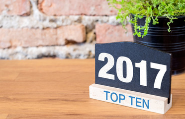 Top ten topic of 2017 year on blackboard sign and green plant on
