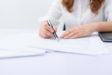 Business woman filling information on document.