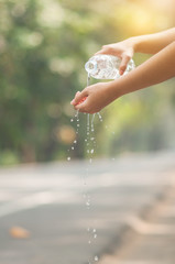 Close up woman hand pouring water from bottle on hand with nature background.