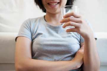 Woman hand holding glass of water for drink.