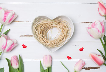 Pink Tulips with heart shaped empty nest, top view, copy space.
