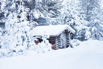 Small wooden blockhouse under snow