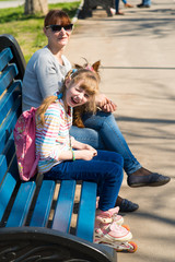 Girl on roller skates sitting on bench