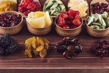 Assortment of dried fruits closeup on brown wooden background. Decorative border of dry exotic fruit in spoons, bowl.
