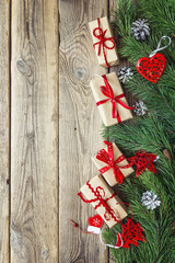 Border from the pine branches, Christmas decorations and gift boxes on an old wooden table. Holidays Christmas background. Space for text or design. Top view.