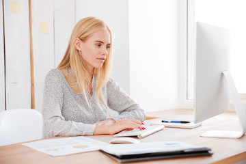 Attractive smiling business woman working with laptop in office