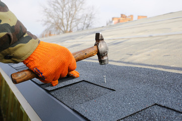 Builder Building Roof. Worker Hammer in Nails on the Roof. Roofer is hammering a Nail in the Roof Shingles. Construction Nails Vapor barrier and Waterproofing. Unfinished roof.