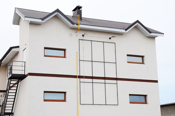 Modern apartment house. chimney on the roof. Coaxial Pipe Heating System House. Individual heating system. Rain gutters on a home. Plastic windows and attic. Construction with metal roof