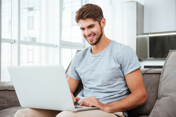 Happy young man sitting on sofa at home with laptop