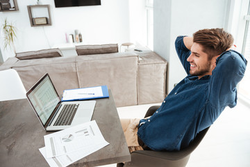 Happy young man stretching at home near laptop