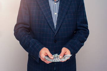 Senior man in suit counting money in hands