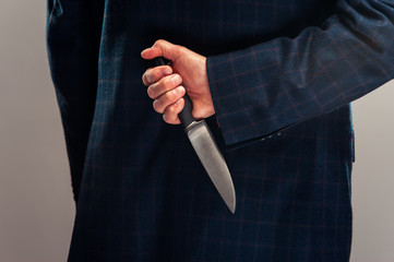 Senior businessman in suit with knife behind back