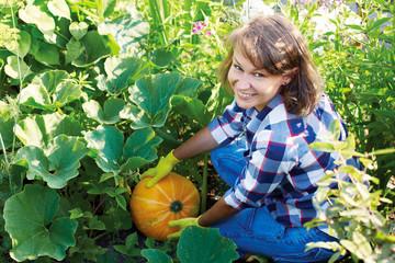 Woman gardener with orange pumpkin in the garden