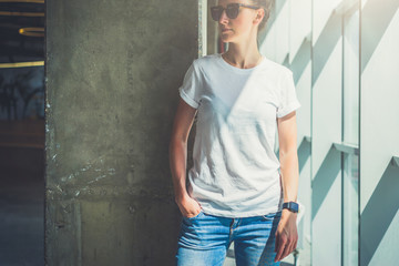 Girl in sunglasses,white T-shirt and blue jeans standing with her hand in pocket jeans in a room against concrete wall next to window. On hand of young woman digital gadget - smartwatch. Mock up.